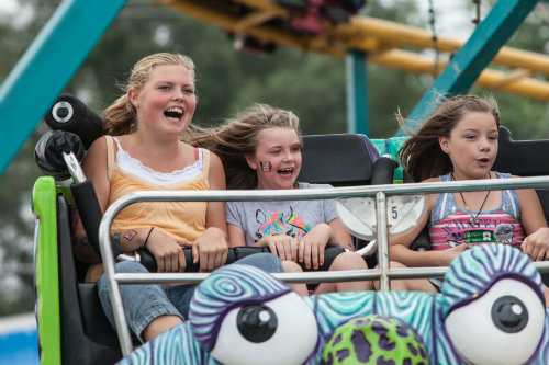 three children having fun on a carnival ride at a fair