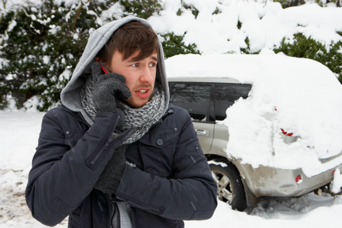 man stranded in the snow making a call