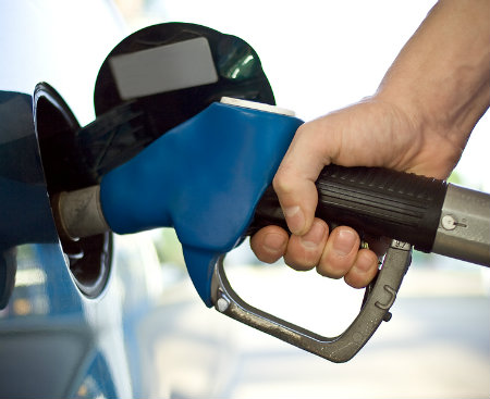pumping gas at gas station in blue car