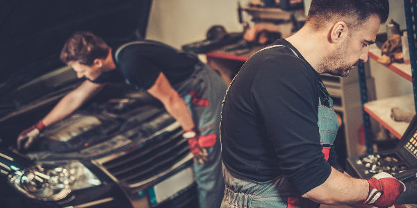 Mechanics working on a vehilce under the hood