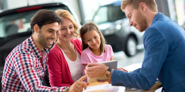 Family at a dealership talking with dealer and smiling happily