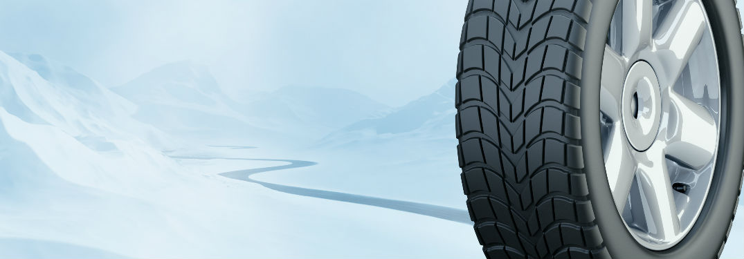 Snow tire pictured against snowy road.