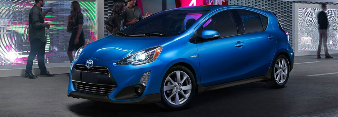 blue 2017 Toyota Prius c parked in city at night