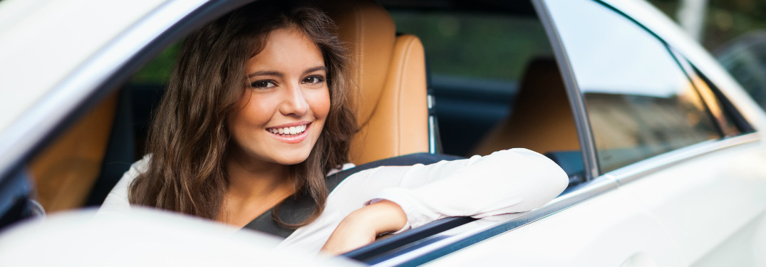 brunette woman in car smiling at camera