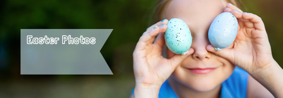 Child holding Easter Eggs in front of eyes for picture