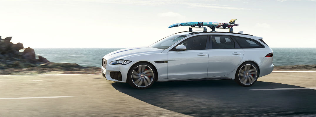 White 2018 Jaguar XF Sportbrake with Surfboard on the Roof on Coast Road