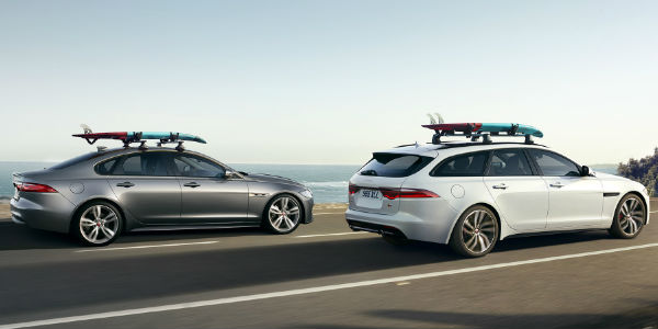 White JaguarXF Sportbrake and Gray Jaguar XF Side By Side on Coast Road