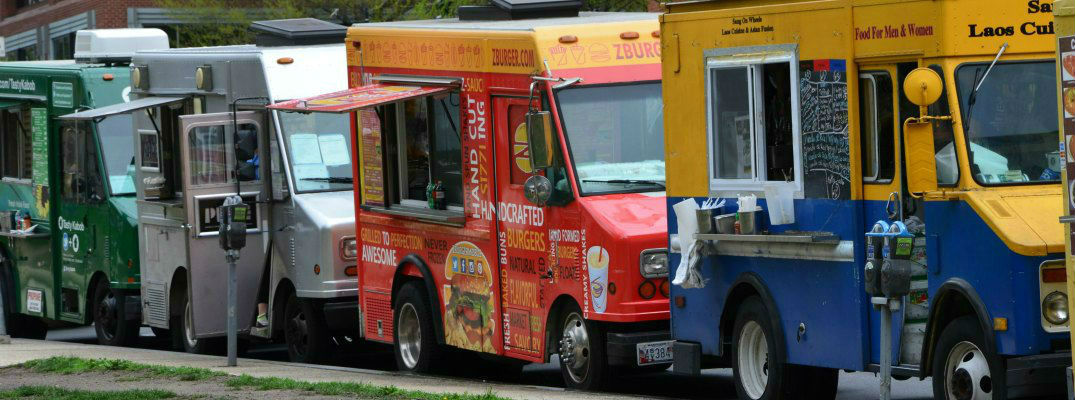 Line of Colorful Local Food Trucks Parked on the curb