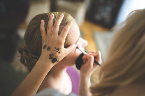 mom putting Halloween face paint on daughter
