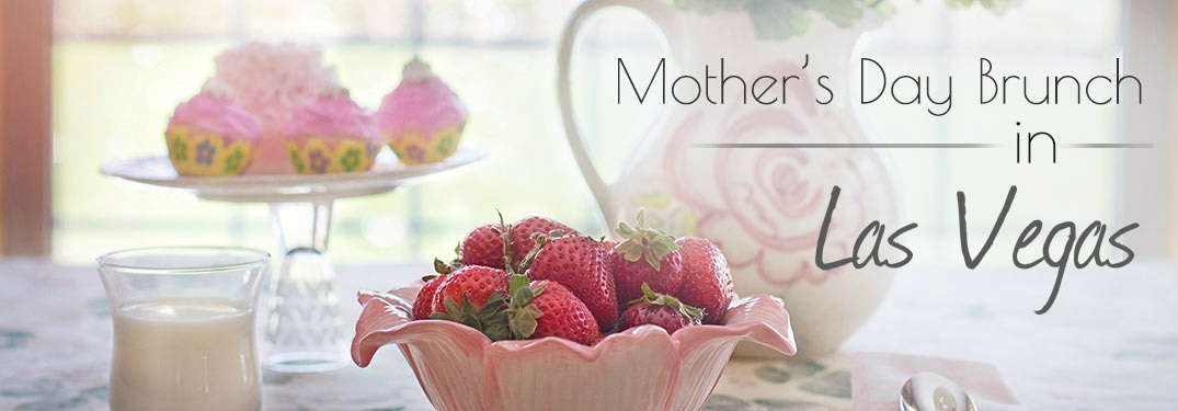 strawberries and cupcakes with a pitcher laid out on a table