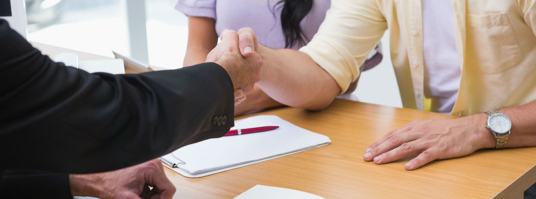 Man and Salesman Shaking Hands After Signing Paperwork
