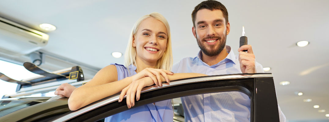 Young Smiling Couple with Keys to new car in dealership showroom