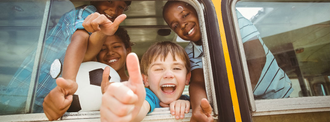 Smiling Kids in School Bus Giving Thumbs Up Out the Window