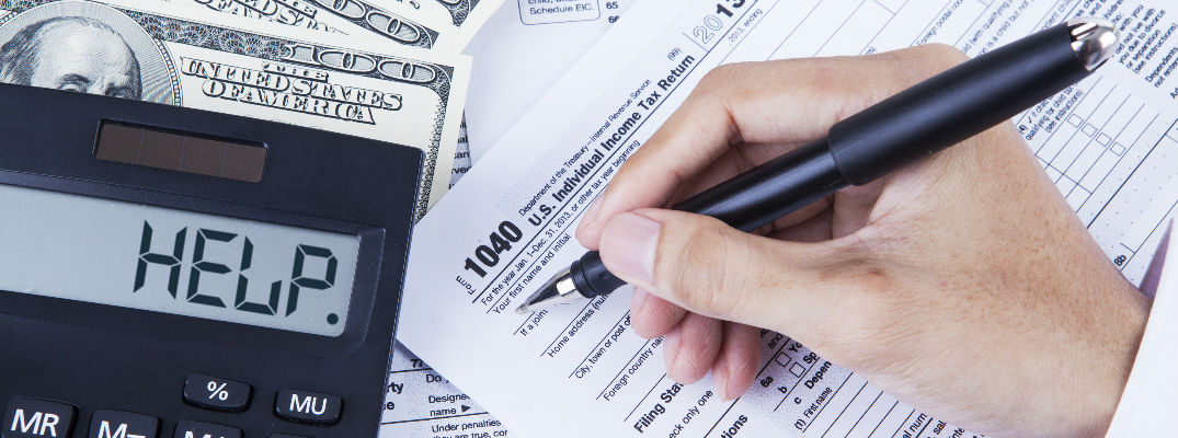 a person holding a pen with tax forms
