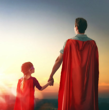 father and daughter dressed up in costume as superheroes
