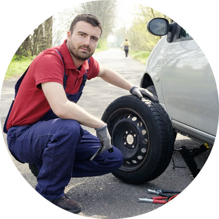 man fixing flat tire on vehicle
