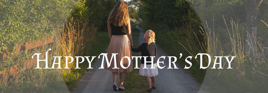 Mother and Daughter Walking on Wooded Road holding hands
