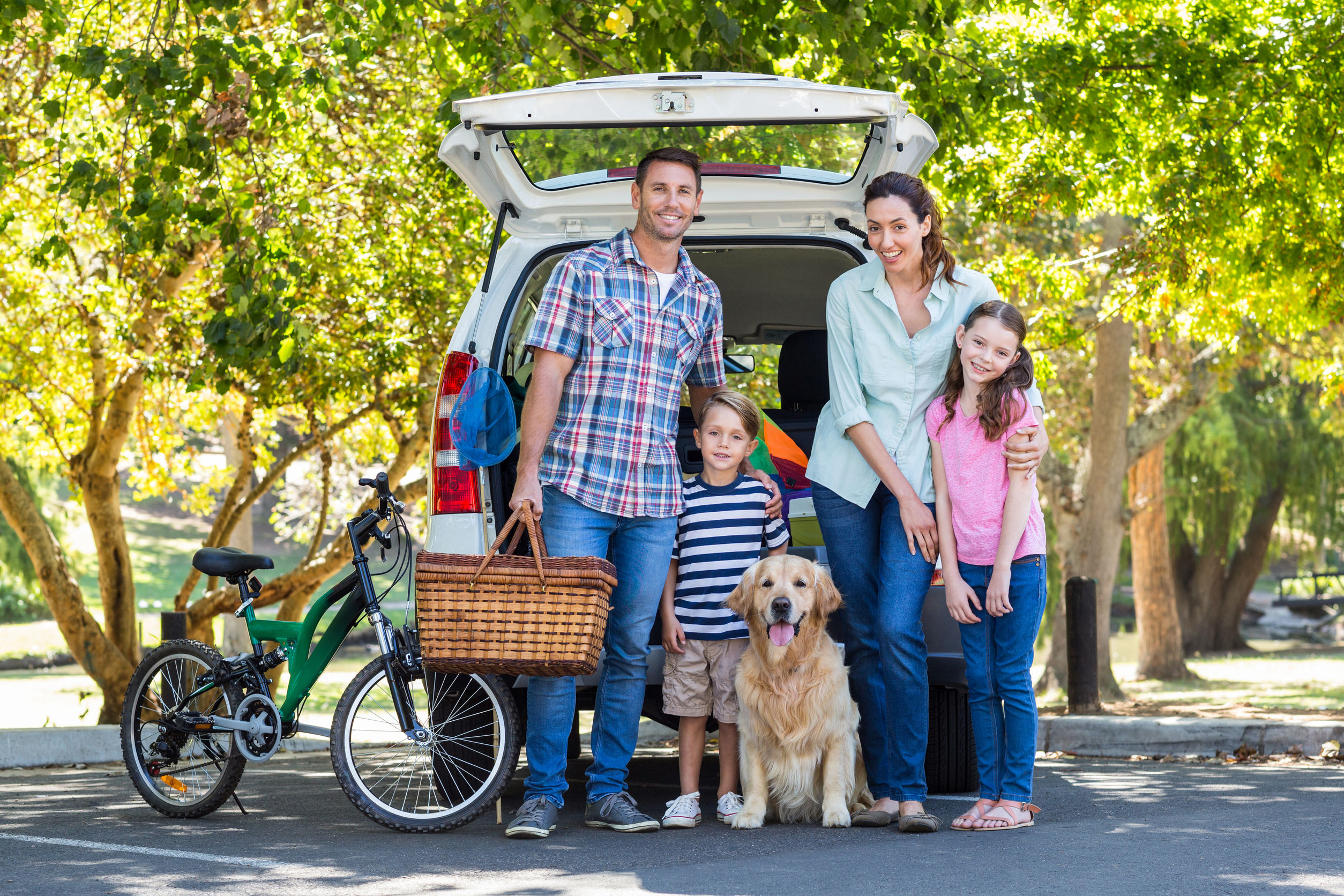 Smiling family and their dog getting ready for a road trip with a bike and picnic basket