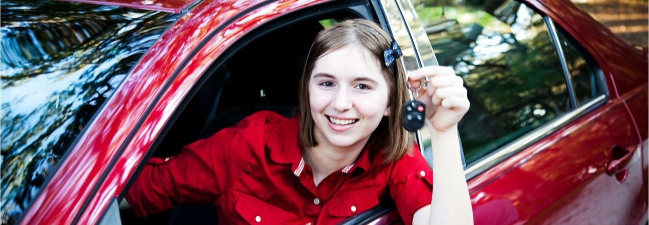 A young driver holding the keys of her sedan out of the window
