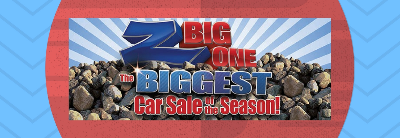 """The words """"Z Big One Sale The Biggest Car Sale of the Season"""" sitting on top of a rock pile"""