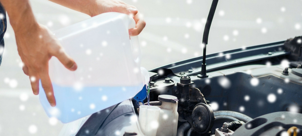 worker adding antifreeze as part of fluid check