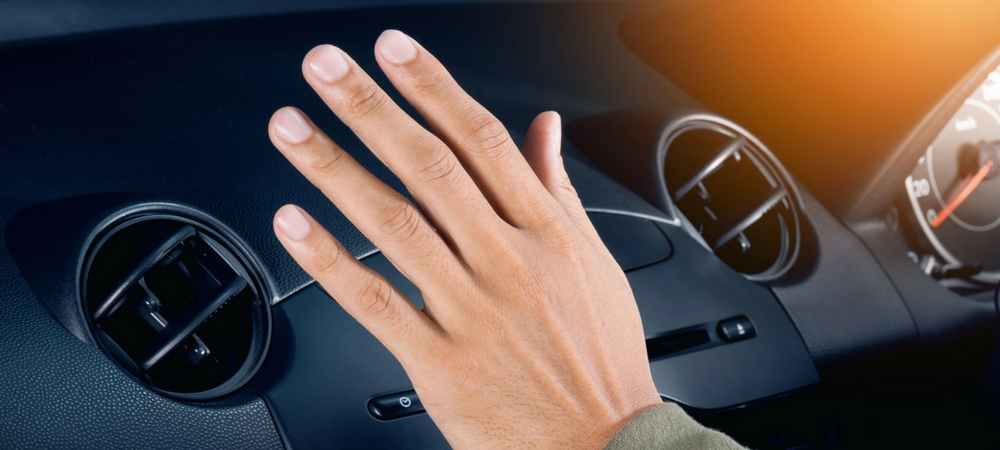 Man's hand over a car's AC vent