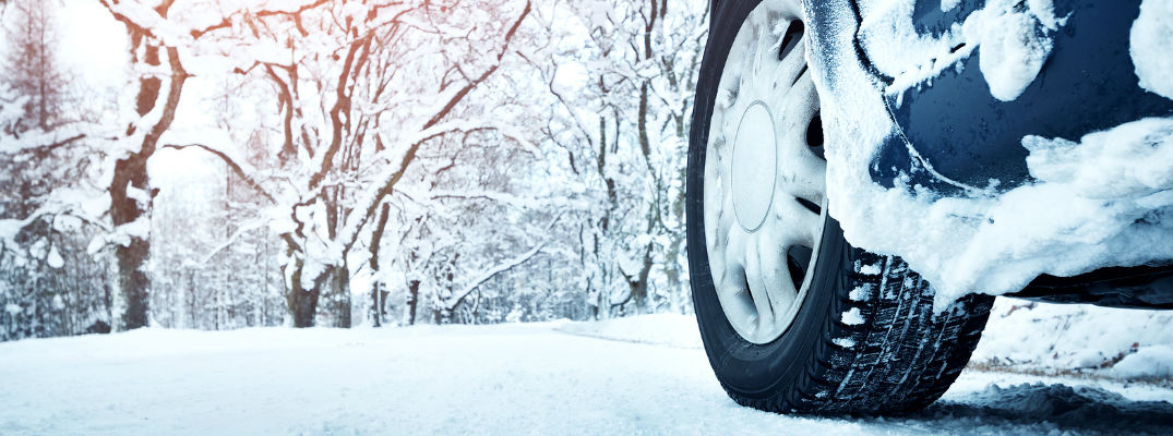 snow-covered tire on snowy road