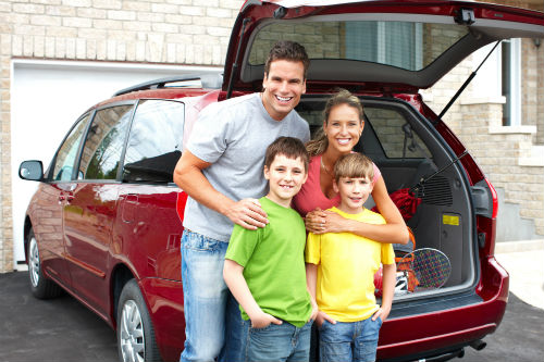 family packing their SUV for a road trip vacation