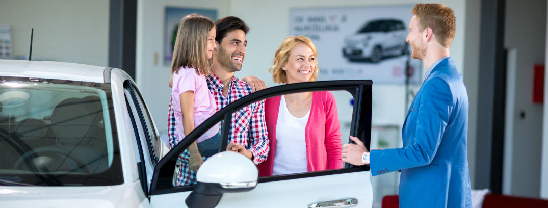 Cheerful family in car showroom