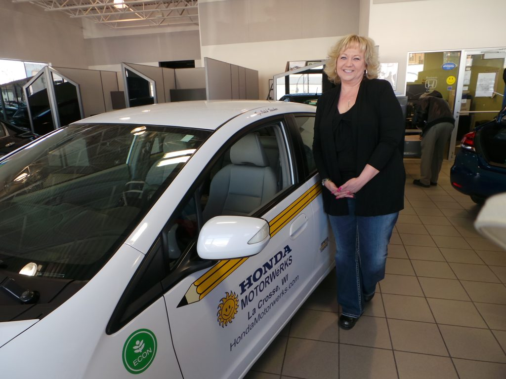 Top notch teacher of the month Jackie Goetsch stands with the Honda Insight Hybrid, her ride for the month of April.