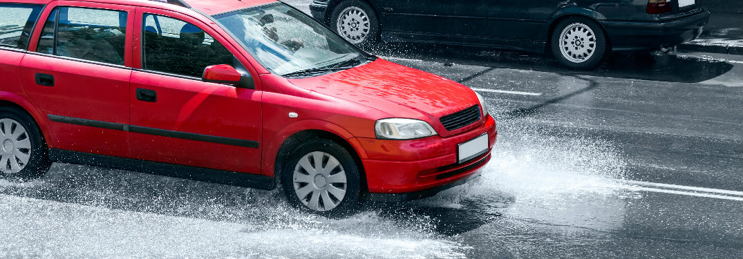 red car driving through flooding street