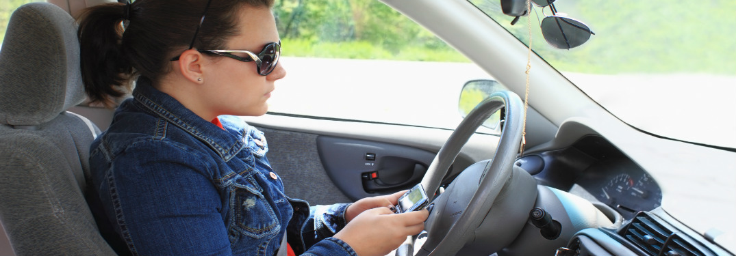 girl wearing sunglasses texting while driving