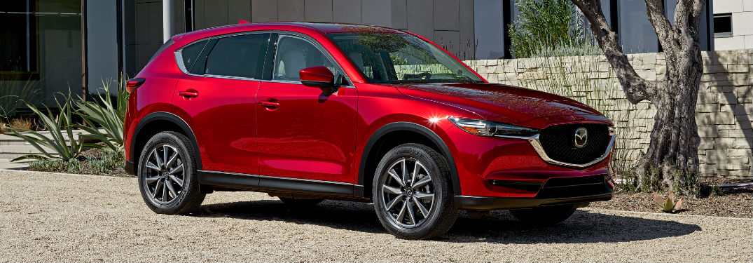 Soul Red Crystal Metallic 2017 Mazda CX-5 parked in front of a house