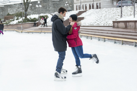 Couple ice skating together outside