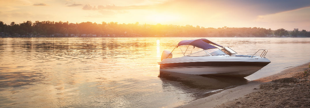 Boat on Sandy beach with sunset background