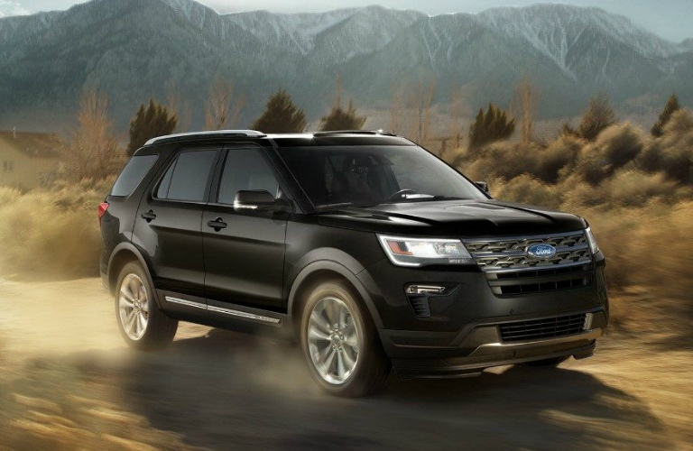 Black 2018 Ford Explorer Driving in Front of Snowy Mountains