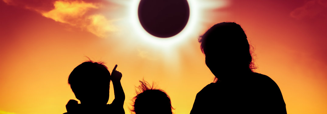 silhouette of a family looking at a solar eclipse
