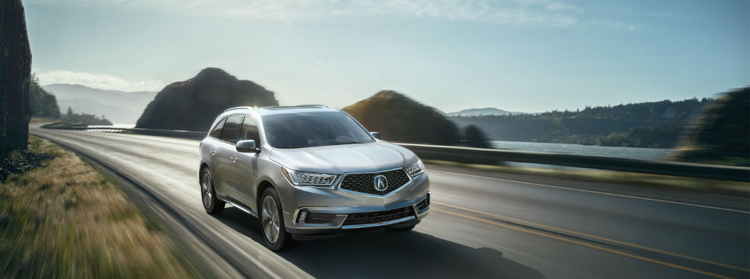 A 2018 Acura MDX coming down the highway in front of a mountainous background
