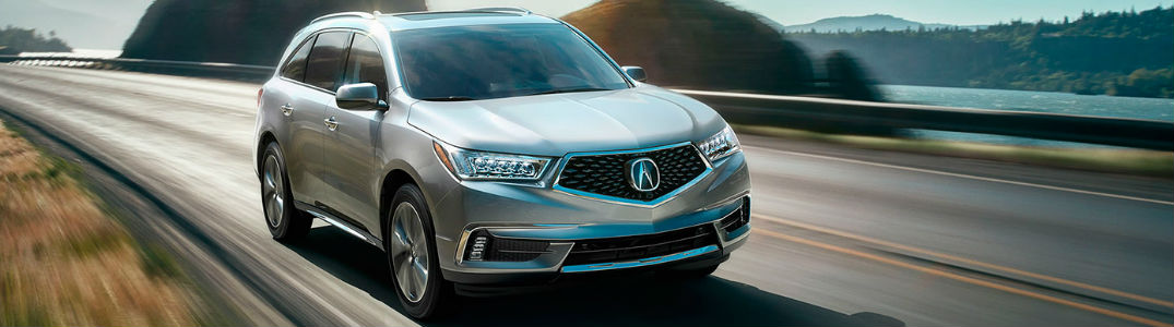 New Acura MDX model driving down a road