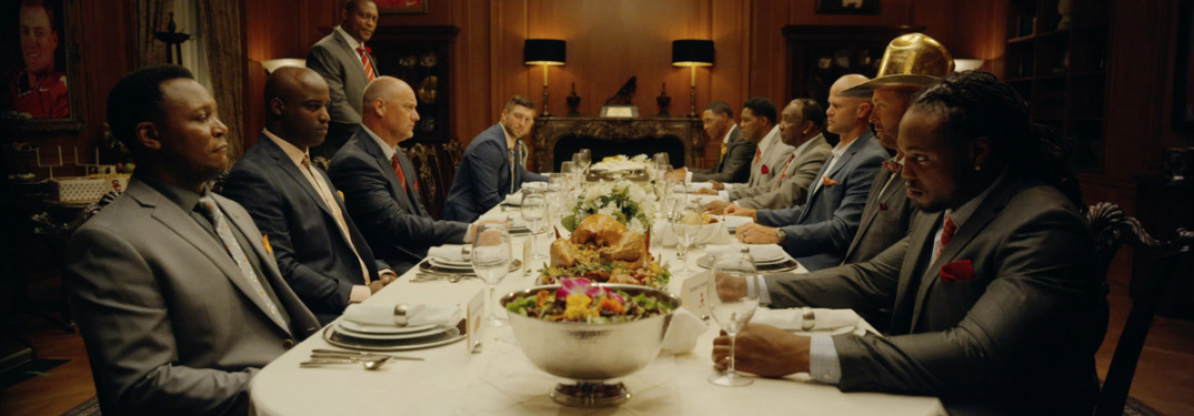 Heisman House members sitting at the dinner table in new commercial