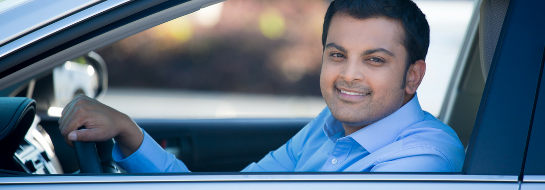 Man smiles through window of car