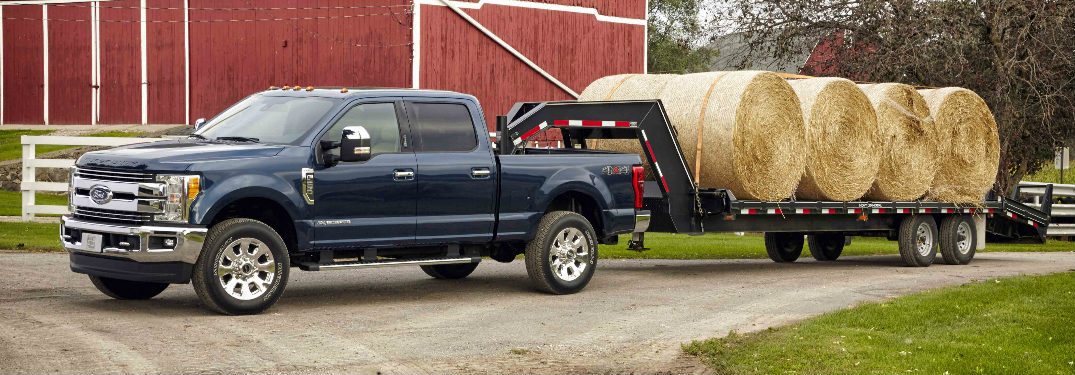 2017 Ford F-250 towing trailer of hay near barn