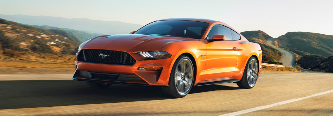 orange 2018 Ford Mustang GT driving on highway exterior front view