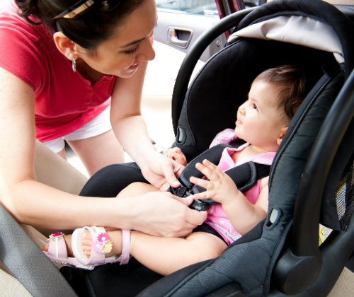 mom puts her child into a car seat correctly