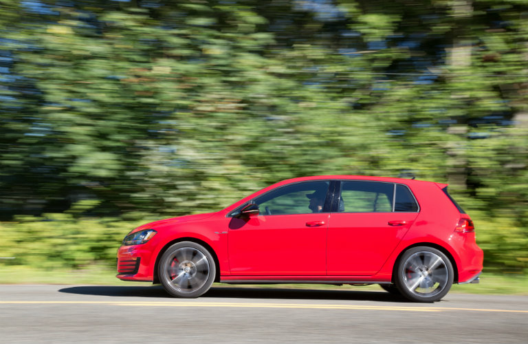 a red 2017 VW Golf GTI driving on the road in front of trees