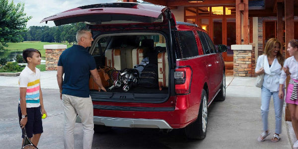Family Loading Cargo Into Rear Of Red  Ford Expedition