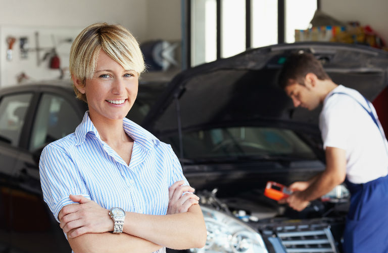 Woman smiles while service technician works on car in background.