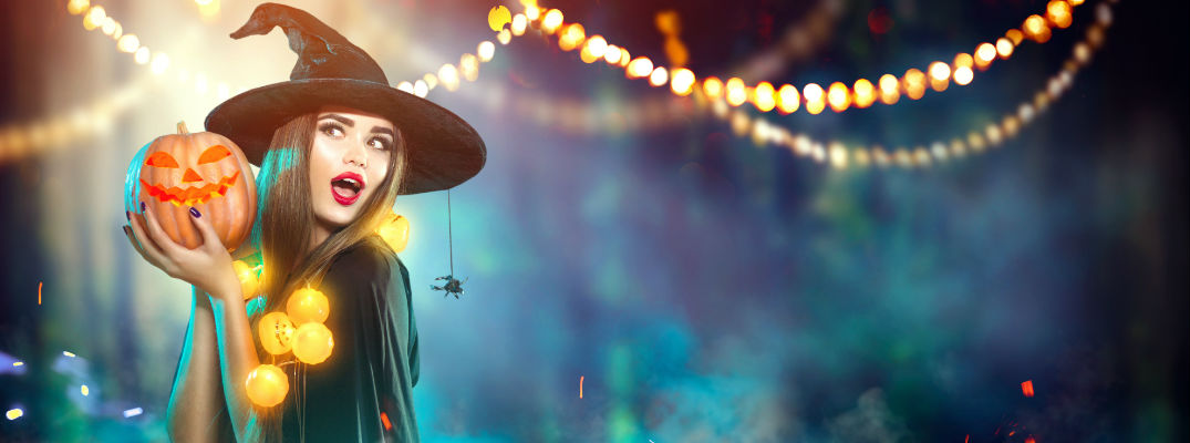 Girl in Witch Costume Holding Pumpkin