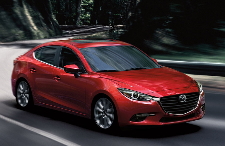 Exterior View Of A Red 2018 Mazda3 Driving Around A Curve On A Country Road