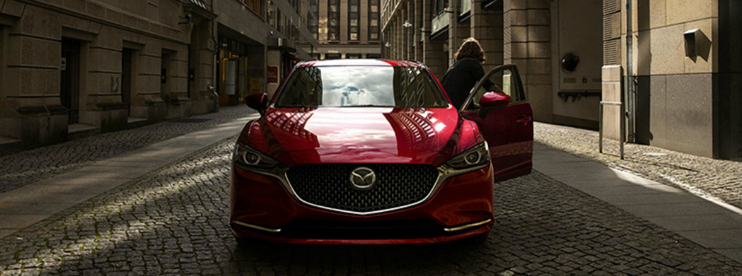 View of the front of a red 2018 Mazda6 with a woman exiting the open driver's side door